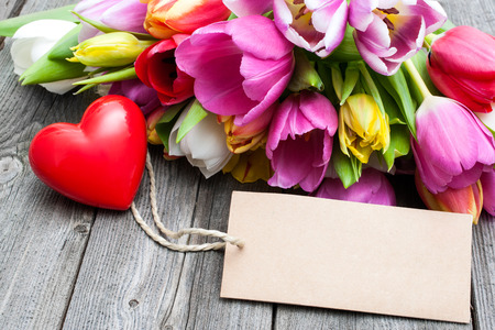 spring message: Bouquet of tulips with an empty tag and red heart on wooden background