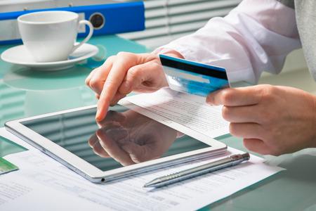 factura: Mujer que usa una tarjeta de crédito y la tableta digital para la compra on-line