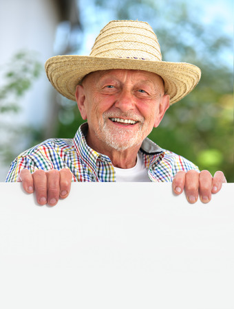 Happy smiling senior man with a straw hat holds a blank board