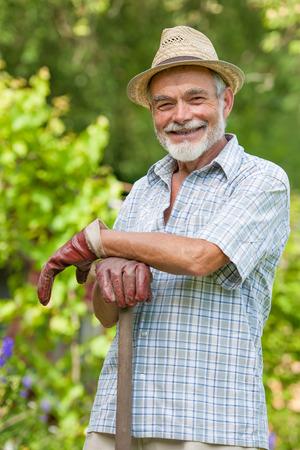 庭のスペードと笑みを浮かべてシニアの肖像画 写真素材