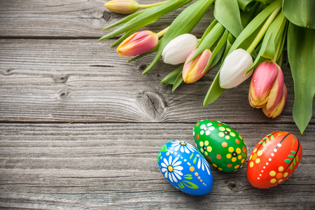 easter decorations: Easter eggs and fresh spring tulips on weathered wooden background