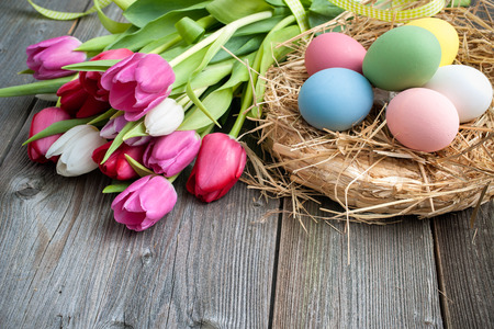 Easter eggs with tulips on weathered wooden background Stock Photo