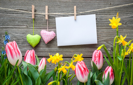 Message and hearts on the clothesline with spring flowers against wooden background photo
