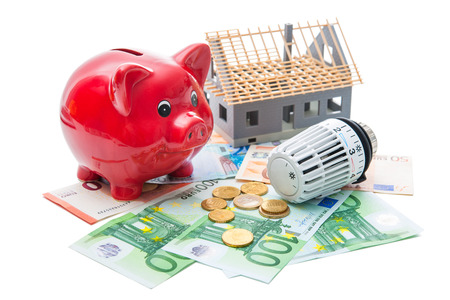 economizing: Heating thermostat with piggy bank and money, expensive heating costs concept