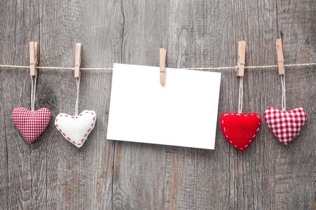 paper heart: Message and red hearts on the clothesline against wooden background