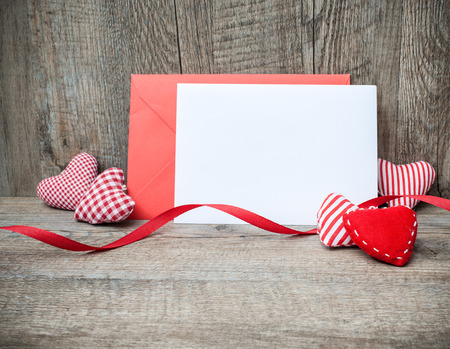 Envelope with red hearts for valentine day on wooden background photo
