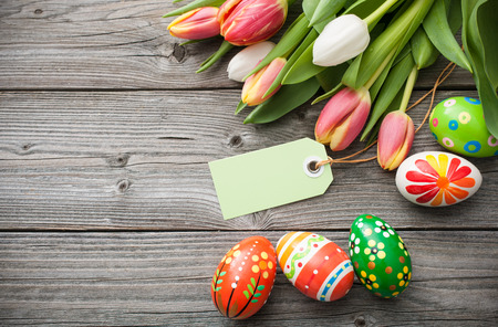 Easter eggs and spring tulips with an empty tag on weathered wooden background Stockfoto