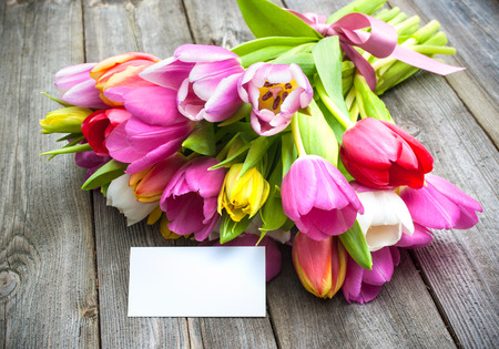 Bouquet of tulips with an empty tag on wooden background