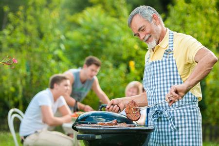 Familia a tener una fiesta barbacoa en su jardín en verano