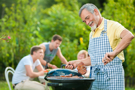 parrillada: Familia a tener una fiesta barbacoa en su jardín en verano