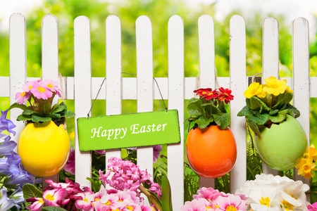 hangs: Sign Happy Easter hangs on the garden fence Stock Photo