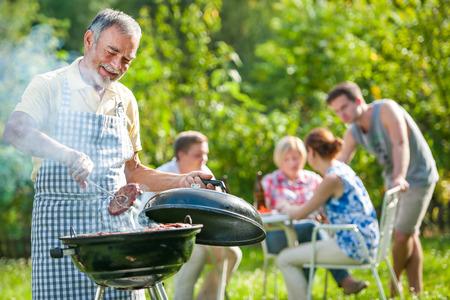 여름에 자신의 정원에서 바베큐 파티를 가족