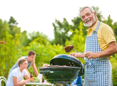 carne asada: Familia a tener una fiesta barbacoa en su jard�n en verano