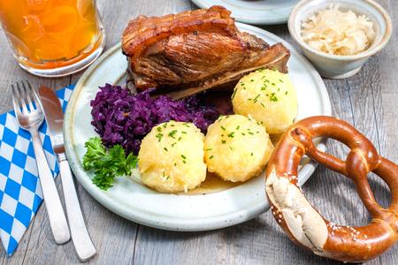 comida alemana: Apetitoso asado bávaro plato de cerdo con albóndigas y pretzel Foto de archivo