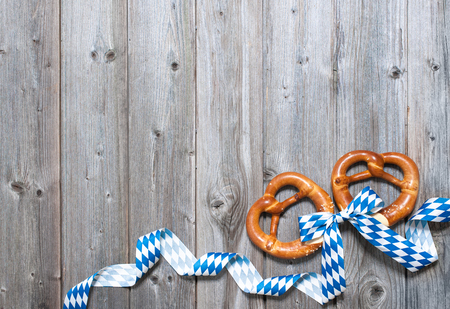 Bavarian pretzels with ribbon on wooden board as a background for Oktoberfest