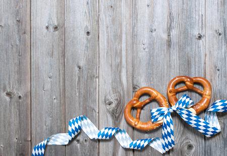 Bavorské preclíky se stuhou na dřevěné desce jako pozadí na Oktoberfest Reklamní fotografie
