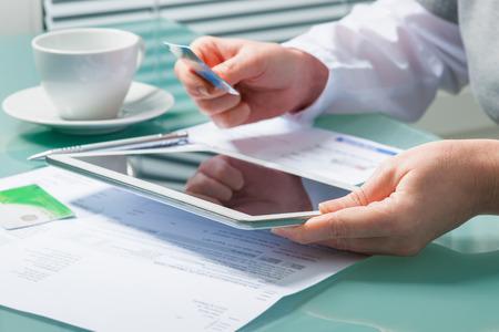 cuenta: Mujer que usa una tarjeta de crédito y la tableta digital para la compra on-line