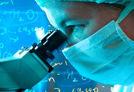 과학자가 실험실에서 현미경을 통해 찾고 스톡 콘텐츠
