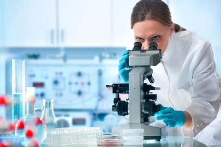 examenes de laboratorio: Científico mirando por un microscopio en un laboratorio Foto de archivo