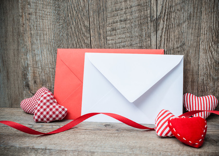 surprises: Envelope with red hearts for valentine day on wooden background