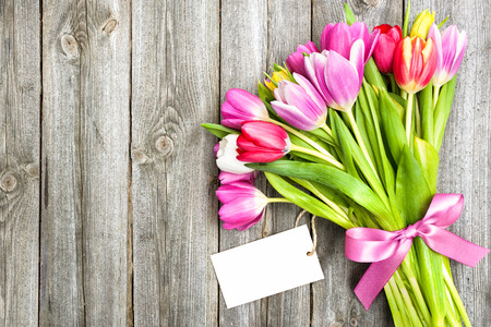 bouquet of spring tulips with empty tag on old wooden background photo