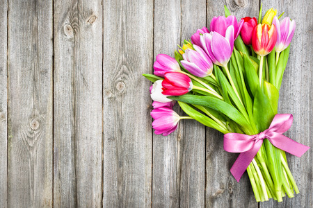 bouquet of spring tulips on old wooden background photo