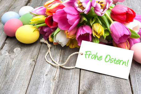 Easter eggs and tulips with a tag on wooden background Stock Photo - 37623495
