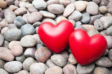 red pebble: Two red hearts on pebble stones, still life. Valentine�s Day background
