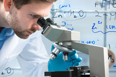 scientist: Scientist looking through a microscope in a laboratory