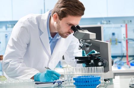 estudiantes medicina: Cient�fico mirando por un microscopio en un laboratorio Foto de archivo