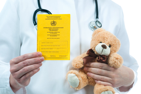 vaccinate: Pediatrician holding an international certificate of the vaccination