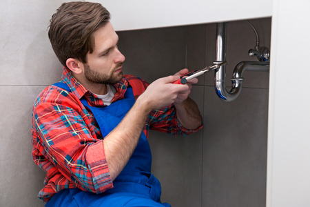 Young plumber is repairing a sink at the bathroom