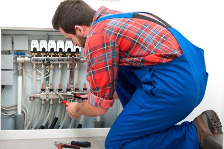 床下から来る暖房の修理技術者 写真素材