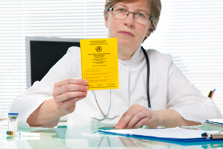 vaccinating: Doctor showing an international certificate of the vaccination Stock Photo