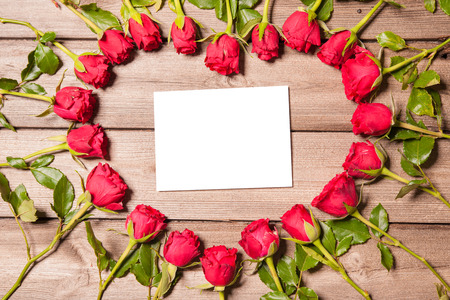 Frame of fresh roses arranged on old wooden background photo