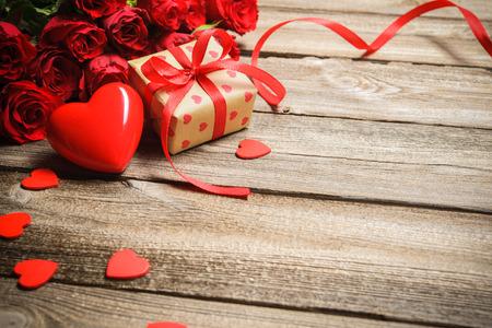 matrimonio feliz: Manojo de rosas con una caja de regalo y corazón rojo sobre fondo de madera