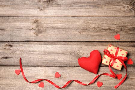 Srdce a dárková krabička s červenou mašlí na dřevěné pozadí