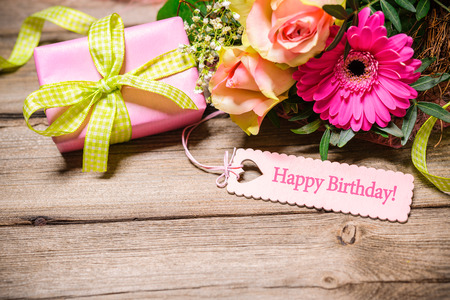 Bunch of flowers and tag with text on wooden background. Happy Birthday