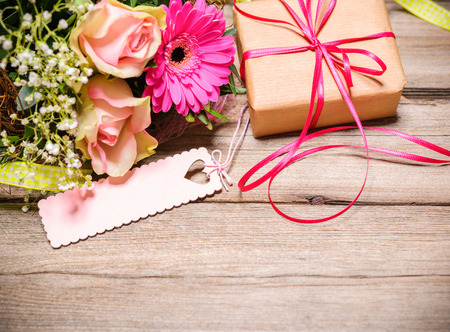 happy day: Bunch of flowers with an empty tag on wooden background