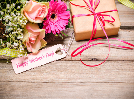 heart gift box: Bunch of flowers and tag with text on wooden background. Happy Mothers Day