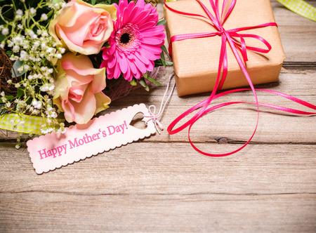 madre: Manojo de flores y etiqueta con el texto en el fondo de madera. Día de madres feliz Foto de archivo