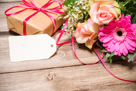 Bunch of flowers with an empty tag on wooden background