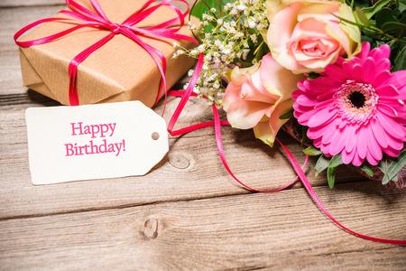 花や木製の背景上のテキストにタグの束。お誕生日おめでとう 写真素材
