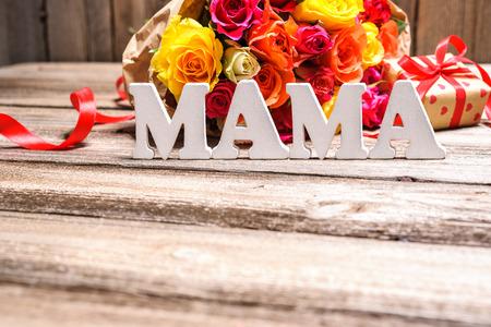 Rosenstrauß mit einem Geschenk-Box und Wort Mama auf Holzuntergrund