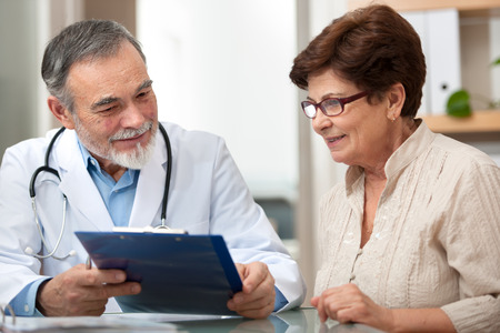 doctor examining woman: doctor talking to his female patient at office Stock Photo