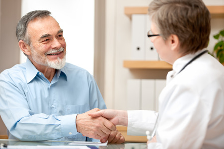 elderly adults: Doctor shaking hands to patient in the office Stock Photo