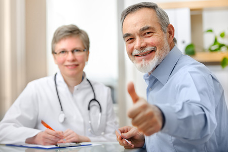 medical doctors: Happy senior patient and doctor at the doctors office