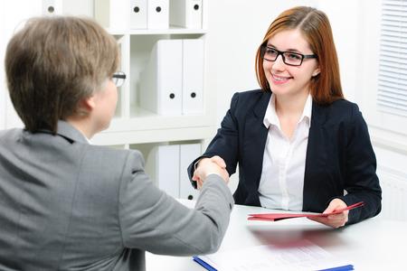 reunion de trabajo: Solicitante de empleo con la entrevista. Apret�n de manos mientras entrevistas de trabajo Foto de archivo
