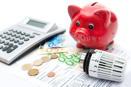 power of savings: Heating thermostat with piggy bank and money, expensive heating costs concept
