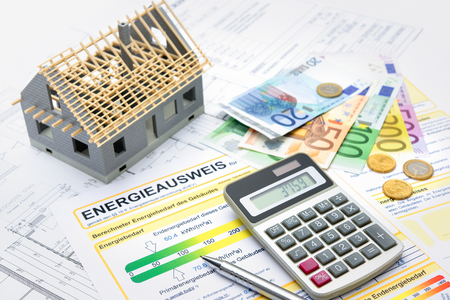 economizing: House with money, calculator and an energy efficiency certificate Stock Photo